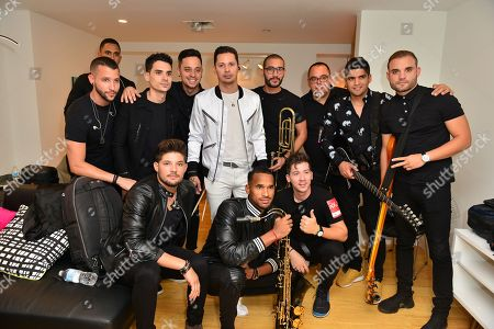 Leoni Torres backstage poses for portrait with his band before performing at James L. Knight Center