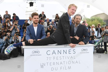 Lukas Dhont, Victor Polster, Arieh Worthalter. Actor Victor Polster, centre, performs a split on the plinth as he poses with director Lukas Dhont, left, and actor Arieh Worthalter during a photo call for the film 'Girl' at the 71st international film festival, Cannes, southern France