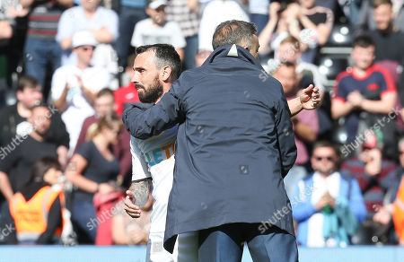 Swansea City manager Carlos Carvalhal with Leon Britton of Swansea City at the end of the match as Swansea City are relegated from the Premier League