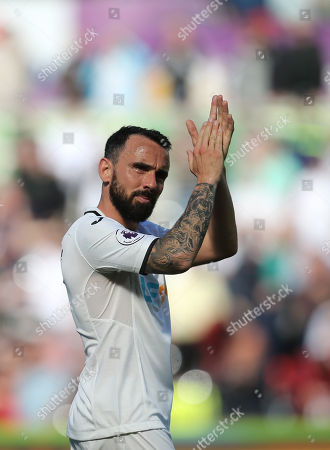 Leon Britton of Swansea City applauds the fans at the end of the match as Swansea City are relegated from the Premier League