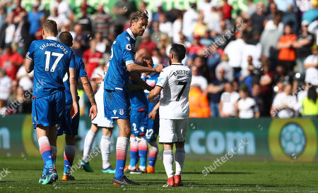 Peter Crouch of Stoke City towers over Leon Britton of Swansea City as the pair shake hands at full time