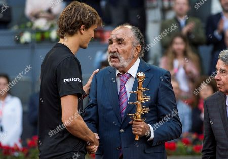 German tennis player Alexander Zverev (L) receives his trophy from Romanian Ion Tiriac, owner of Mutua Madrid Open, as he celebrates his victory over Austrian Dominic Thiem at the end of their Mutua Madrid Open Men's final match at Caja Magica in Madrid, Spain, 13 May 2018.