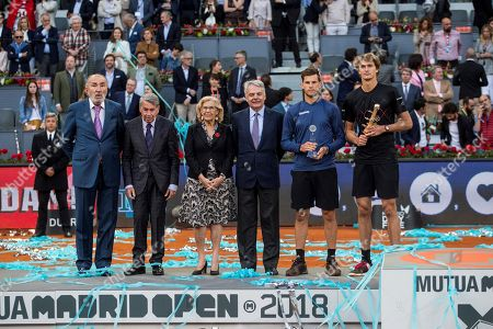 German tennis player Alexander Zverev (R), next to Madrid's Mayoress, Manuela Carmena (3L), owner of Mutua Madrid Open, Romanian Ion Tiriac (L), director of the tournament, Manolo Santana(2L), and President of Mutua Madrilena, Ignacio Garralda (3R),celebrates his victory over Austrian Dominic Thiem (2R) at the end of their Mutua Madrid Open Men's final match at Caja Magica in Madrid, Spain, 13 May 2018.