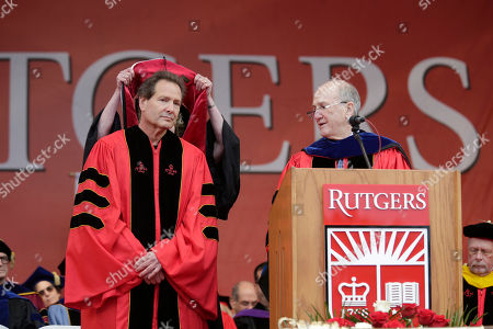 Dan Schulman, CEO of PayPal, left, receives an honorary degree during a Rutgers University graduation ceremony in Piscataway Township, N.J., . Family and friends watched as over 18,000 graduates received their degrees on Mother's Day