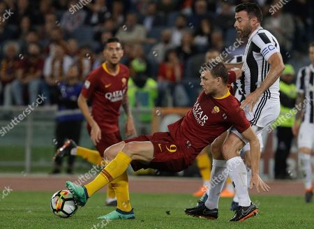 Juventus' Andrea Barzagli, right, challenges Roma's Edin Dzeko during a Serie A soccer match between Roma and Juventus, at the Rome Olympic stadium