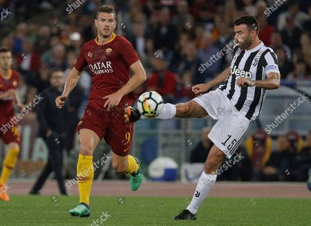 Juventus' Andrea Barzagli clears the ball as Roma's Edin Dzeko looks, during a Serie A soccer match between Roma and Juventus, at the Rome Olympic stadium