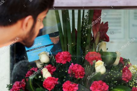 A man peeks inside a security guard house displaying a boutique of flowers with a greeting card with a picture of new Malaysian Prime Minister Mahathir Mohamad at the Perdana Leadership Foundation in Putrajaya, Malaysia, . Shares of regional budget airline AirAsia plunged Monday after its chief Tony Fernandes apologized for supporting defeated Prime Minister Najib Razak in a historic election last week that ended with a victory for a four-party alliance led by Mahathir Mohamad