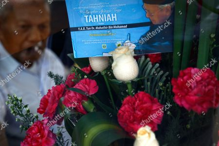 A man sits inside a security guard house displaying a boutique of flowers with a greeting card baring a picture of new Malaysian Prime Minister Mahathir Mohamad at the Perdana Leadership Foundation in Putrajaya, Malaysia, . Shares of regional budget airline AirAsia plunged Monday after its chief Tony Fernandes apologized for supporting defeated Prime Minister Najib Razak in a historic election last week that ended with a victory for a four-party alliance led by Mahathir Mohamad