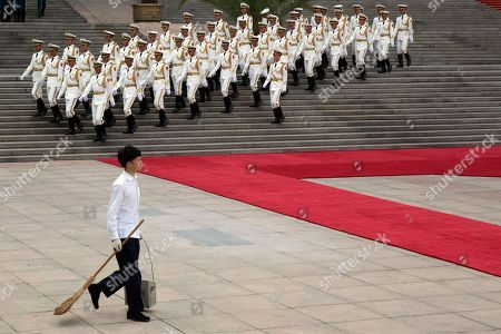 A cleaner walks past as members of a Chinese honor guard march down the steps of the Great Hall of the People before a welcome ceremony for Trinidad and Tobago Prime Minister Keith Rowley in Beijing, China