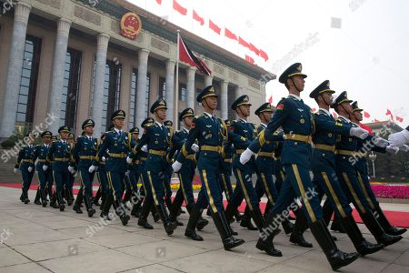 Members of a Chinese honor guard march in front of the Great Hall of the People before a welcome ceremony for Trinidad and Tobago Prime Minister Keith Rowley in Beijing, China