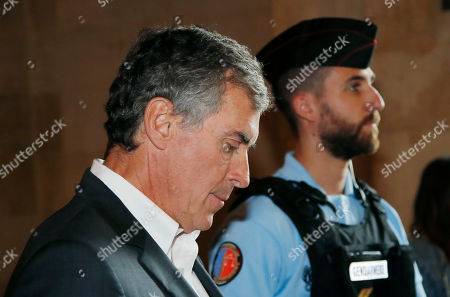Stock Picture of Former French budget Minister Jerome Cahuzac, escorted by a police officer, arrives at Paris court house in Paris, France, . A former French budget minister, who was in charge of fighting tax evasion in the country, has been again convicted of tax evasion and money laundering but received a reduced sentence at his appeal trial