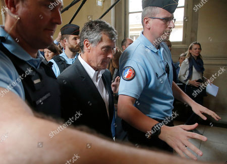 Former French budget Minister Jerome Cahuzac, escorted by police officers, leaves the Paris court house in Paris, France, . A former French budget minister, who was in charge of fighting tax evasion in the country, has been again convicted of tax evasion and money laundering but received a reduced sentence at his appeal trial