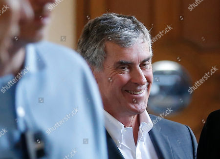 Former French budget Minister Jerome Cahuzac smiles as he leaves the Paris court house in Paris, France, . A former French budget minister, who was in charge of fighting tax evasion in the country, has been again convicted of tax evasion and money laundering but received a reduced sentence at his appeal trial