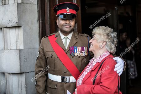 Victoria Cross recipient Johnson Beharry, left, greets guest Cynthia Rolfe at a service in support of the Victoria Cross and George Cross Association, at St Martin-in-the-Fields in London, . Twenty recipients of the Victoria Cross or the George Cross, along with widows and families of those who have posthumously received the honours, have been remembered at a special service