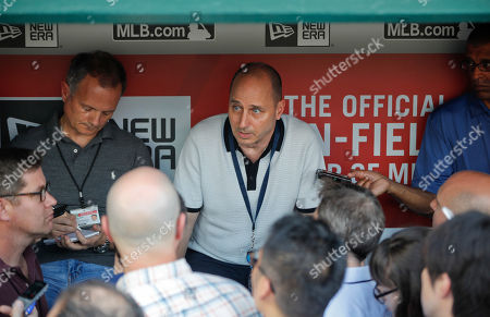 New York Yankees General Manager is Brian Cashman, center, talks with members of the media in the dugout prior to the start of an interleague baseball game between the New York Yankees and Washington Nationals at Nationals Park, in Washington