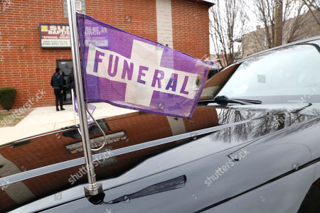 Stock Photo of A funeral flag waves on a hearse outside a church on Chicago's West Side, during the service for 16-year-old Jaheim Wilson, who was shot and killed a few days earlier. Wilson was a cousin of Alexis Willis, who is a Peace Warrior at North Lawndale College Prep High School