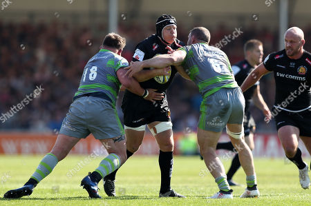Thomas Waldrom of Exeter Chiefs is tackled by David Wilson and Mark Wilson of Newcastle Falcons
