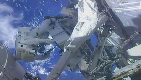 In this frame from NASA TV, NASA astronaut Ricky Arnold, left, and NASA astronaut Drew Feustel work on shuffling around a couple of space station pumps at the International Space Station on