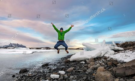 MODEL RELEASED Hiker jumps, ice floes at the edge of the glacier lagoon Joekulsarlon, glacial lake, sunset, southern edge of Vatnajoekull, southeastern Iceland, Iceland
