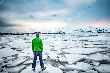 MODEL RELEASED Hiker on an ice floe, glacier lagoon Joekulsarlon, glacial lake, sunset, southern edge of Vatnajoekull, southeast Iceland, Iceland