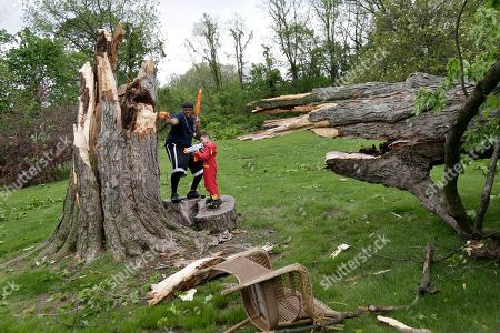 Ryan Lee plays with his son Chris Lee, 5, around a large tree that was damaged during a storm in Newburgh, N.Y., . Powerful storms pounded the Northeast on Tuesday with torrential rain and marble-sized hail, leaving at least two people dead and hundreds of thousands of homes and businesses without power