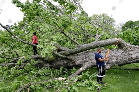 Ryan Lee, right, and Christen Lee play with their son around two large trees that were damaged during a storm in Newburgh, N.Y., . Powerful storms pounded the Northeast on Tuesday with torrential rain and marble-sized hail, leaving at least two people dead and hundreds of thousands of homes and businesses without power