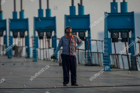 A man works on the Shanghai-Nantong Yangtze River Bridge in Nantong, Jiangsu Province, China, 16 May 2018. Due for completion in 2019, the Shanghai-Nantong Yangtze River Bridge will take its place in the list of mega-bridges. Pylon of the bridge will be with 325 m height the tallest pylon on earth. Shanghai-Changjiang River Bridge is a new Shanghai-controlled railway project, with total length of 11,072 meters. The link will be the world's tallest dual-use cable-stayed bridge, with main span of 1,092 meters. The bridge is divided into two layers, the lower with 4-line railway, the upper with 6-lane highway. Diamond-type concrete bridge pylons are 325 meters high. Based on the world's largest deep water sink foundation equivalent to 12 basketball courts and 115 meters depth. The bridge can withstand the impact of a force 14 typhoon , magnitude 8 earthquake, and the collision of 100  000 dwt ship.The new traffic link is part of the efforts to create a new economic zone around Shanghai, China's trade centre and home to some 25 million people. When completed, the bridge will cut journey time between Shanghai and Nantong from two hours to one.