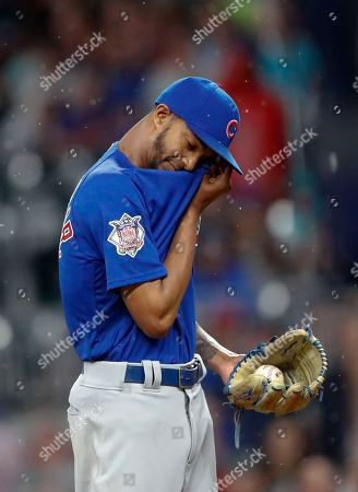 Chicago Cubs relief pitcher Carl Edwards Jr. dries his face between batters during the eighth inning of the team's baseball game against the Atlanta Braves, in Atlanta. The Braves won 4-1