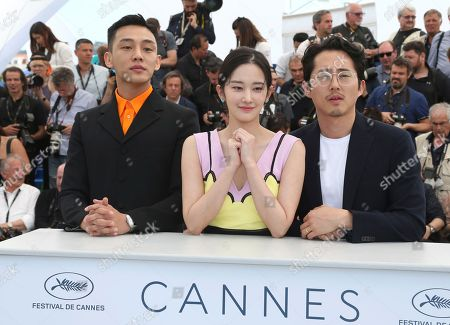 Actor Ah-in Yoo, Jong-seo Jeon, Steven Yeun. Actors Ah-in Yoo, from left, Jong-seo Jeon, and Steven Yeun pose for photographers during a photo call for the film 'Burning' at the 71st international film festival, Cannes, southern France