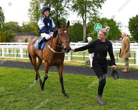 Stock Photo of Winner of The Shadwell Stud Racing Excellence Apprentice Handicap Moorovertheridge left ridden by Harry Burns and trained by Grace Harris is led into the winners enclosure during Afternoon Racing at Salisbury Racecourse on 17th May 2018