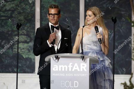 Gabriel Mach (L) and Jacinda Barrett conduct the auction during the auction dinner of the Cinema Against AIDS amfAR gala 2018 held at the Hotel du Cap, Eden Roc in Cap d'Antibes, France, 17 May 2018. The aucton is part of the 71st annual Cannes Film Festival that runs from 08 to 19 May.