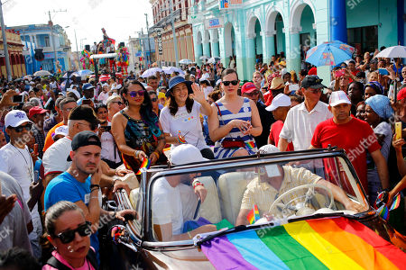 Stock Picture of Mariela Castro, daughter of Raul Castro and director of Cuba's National Center for Sexual Education, waves from a convertible classic car as she sits next to Chilean actress Daniela Vega, center right, during a parade marking the International Day Against Homophobia, Transphobia and Biphobia, in Pinar Del Rio, Cuba