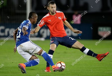 Juan Salazar of Colombia's Millonarios, left, fights for the ball with Gaston Silva of Argentina's Independiente during a Copa Libertadores soccer match in Bogota, Colombia