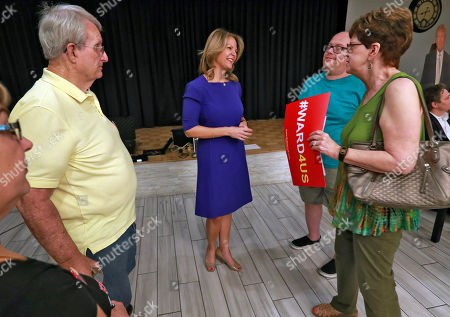 U.S. Senatorial candidate Kelli Ward, center, speaks to volunteers and voters after the Sun Lakes Republican Club meeting in Sun Lakes, Ariz. Shortly before the raffle for a handgun, top Arizona Republicans gave a warning to the crowd gathered at the conservative group's meeting in a retirement community at the edge of Phoenix's sprawl: The Democrats are coming