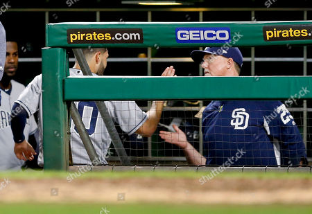 Eric Hosmer, Mark McGwire. San Diego Padres' Eric Hosmer, left, is greeted by bench coach Mark McGwire after scoring on a hit by Franchy Cordero during the sixth inning of a baseball game against the Pittsburgh Pirates, in Pittsburgh