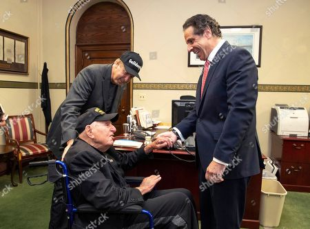 In this photo provided by the Office of the Governor of New York, Governor Andrew M. Cuomo, right, shakes hands with World War II veteran Sidney Walton at the Capitol in Albany, N.Y., . The 99-year-old World War II veteran who regretted skipping the chance to meet some of the nation's last Civil War veterans in 1940 is on a mission to visit all 50 states so people who've never met a WWII vet can finally meet one. Standing at left is Walton's son, Paul Walton
