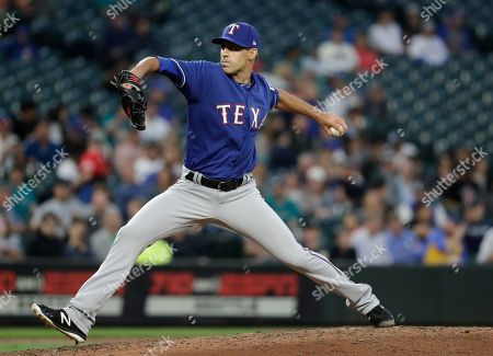 Texas Rangers relief pitcher Brandon Mann throws against the Seattle Mariners in the fourth inning of a baseball game, in Seattle