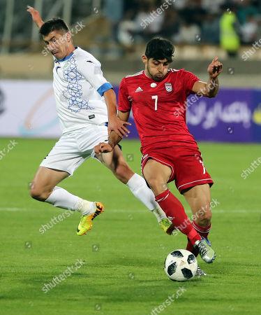 Iran's Mehdi Torabi  (R) in action against Uzbekistan's Akron Komilov (l) during a FIFA friendly soccer match between Iran and Uzbekistan at the Azadi Stadium in Tehran, Iran, 19 May 2018.