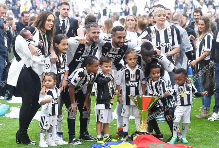Juventus'  Miralem Pjanjc, Medhi Benatia (C) and Blaise Matuidi (R) and family poses with the trophy after winning the Italian Serie A Championship (Scudetto) at the end of the Italian Serie A soccer match Juventus FC vs Hellas Verona FC at Allianz Stadium in Turin, Italy, 19 May 2018.