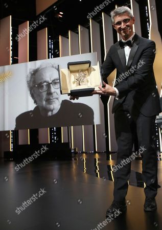 Cinematographer Fabrice Aragno, right, holds the special Palme d'Or award on behalf of director Jean-Luc Godard, on screen, for his film 'The Image Book' during the closing ceremony of the 71st international film festival, Cannes, southern France