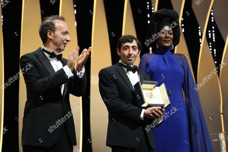 Marcello Fonte, centre, holds the Best Actor award for the film 'Dogman' which was presented by Roberto Benigni, left, and jury member Khadja Nin during the closing ceremony of the 71st international film festival, Cannes, southern France