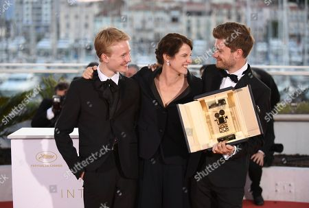 Actor Victor Polster from left, Camera d'Or jury head Ursula Meier and director Lukas Dhont pose with the Camera d'Or award for the film 'Girl' during a photo call following the awards ceremony at the 71st international film festival, Cannes, southern France