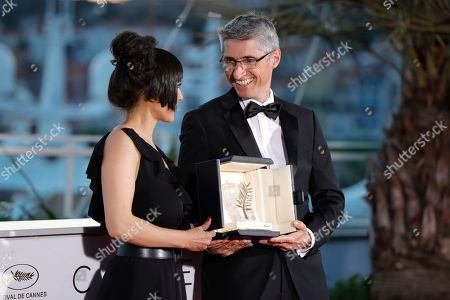Stock Image of Cinematographer Fabrice Aragno poses with the Special Palme d'Or award on behalf of director Jean-Luc Godard for his film 'The Image Book' (Le Livre D'Image) and Mitra Farahani stands next to him at the photocall the Palme D'Or Winner