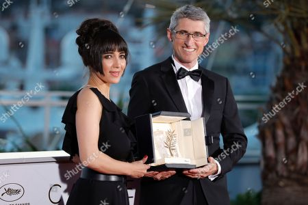 Stock Picture of Cinematographer Fabrice Aragno poses with the Special Palme d'Or award on behalf of director Jean-Luc Godard for his film 'The Image Book' (Le Livre D'Image) and Mitra Farahani stands next to him at the photocall the Palme D'Or Winner