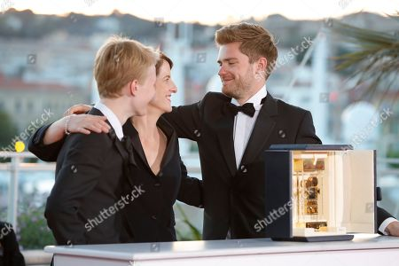 Un Certain Regard Best Performance winner Victor Polster for his role in 'Girl' poses with the Camera d'Or winning Director Lukas Dhont and Camera d'Or jury head Ursula Meier at the Palme D'Or Winner Photocall