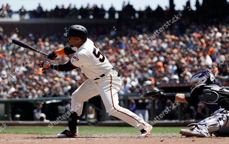 San Francisco Giants' Miguel Gomez drives in a run with a single during the third inning of a baseball game against the Colorado Rockies, in San Francisco