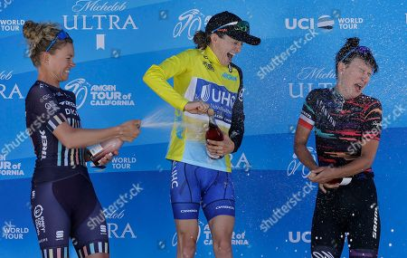 Stock Image of Taylor Wiles, Katie Hall, Kasia Niewiadoma. Katie Hall, center, the winner of the Amgen Tour of California Women's cycling race, is sprayed by second-place finisher Tayler Wiles, in Sacramento, Calif. Third-place finisher Kasia Niewiadoma, right, reacts