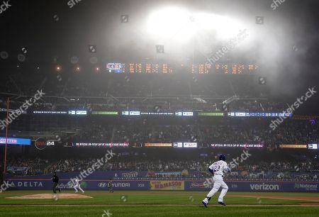 New York Mets' Adrian Gonzalez (23) makes his way up the first base line on a fly-out to left field as a blanket of fog hangs over CitiField during the sixth inning of a baseball game against the Arizona Diamondbacks, in New York