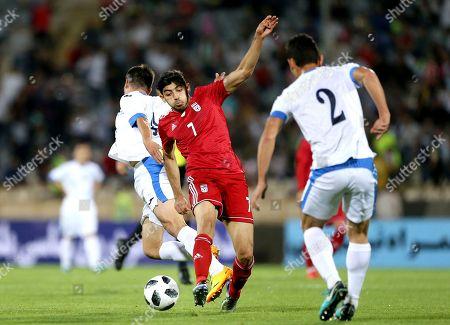 Iran's Mehdi Torabi, center, controls the ball during the international friendly soccer match between Iran and Uzbekistan at the Azadi Stadium in Tehran, Iran