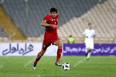 Iran's Mehdi Torabi plays the ball during an international friendly soccer match between Iran and Uzbekistan at the Azadi Stadium in Tehran, Iran
